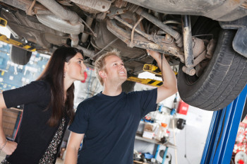 Servicing car - mechanic and woman