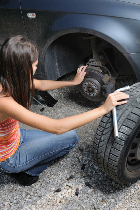 Image of a lady changing a car wheel