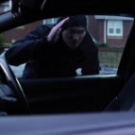 Car thief looking through car window